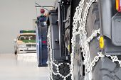 picture of smuggling  - Close up of truck wheels with snow chains and a German police car behind