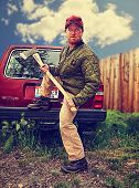 stock photo of hillbilly  - a redneck man with an axe in his hands toned with a retro vintage instagram filter effect - JPG