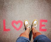 stock photo of v-day  - two feet making a sign for the letter V in the word love - JPG