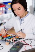 foto of microprocessor  - girl student studying electronic device with a microprocessor - JPG