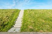 foto of dike  - A concrete staircase between the grass of a dike on a sunny day in autumn - JPG