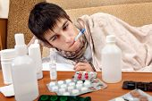 image of home remedy  - Sick Teenager on the Sofa at the Home with Pills on foreground - JPG