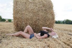 stock photo of shepherdess  - Beautiful young blonde woman outdoors near haystacks - JPG