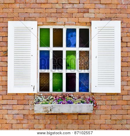 Brick Wall With Colorful Glasses In White Window And Beautiful Flowers