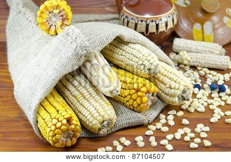 Dried Corn Cobs In A Bag On A Wooden Table