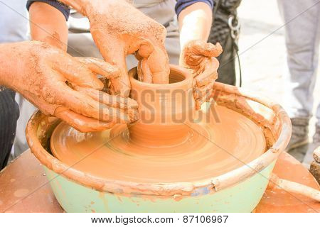Hands working on pottery wheel.