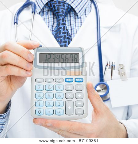 Doctor Holding Calculator In Hands - Health Care Concept - Studio Shot