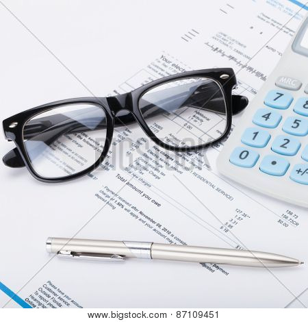 Calculator With Pen, Glasses And Utility Bill Under It