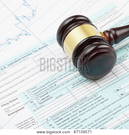 Wooden Judge's Gavel Over Tax Form