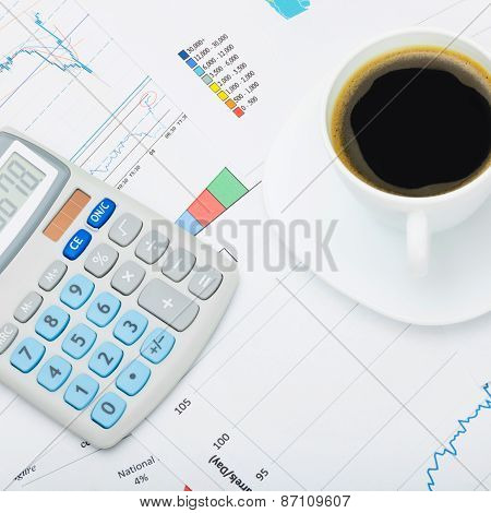 Coffee Cup And Calculator Over World Map And Financial Charts