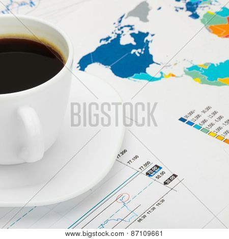 Coffee Cup Over World Map And Some Market Charts