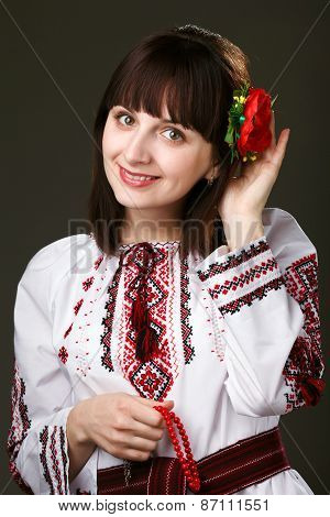 beautiful woman in an embroidered shirt with flower in hair