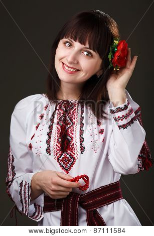 charming woman in an embroidered shirt with flower in hair