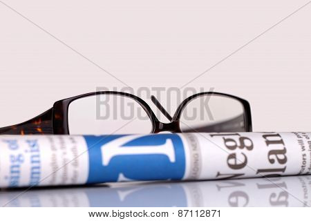 Newspapers And Glasses Lying On Table
