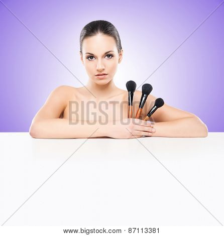 Beauty portrait of young, attractive, fresh, healthy and natural woman with a makeup brushes and a blank billboard