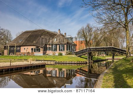 Old Farm With Reflection In The Water In Giethoorn
