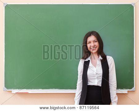 Student Girl Standing Near Clean Blackboard