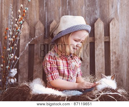 Portrait Of An Adorable Baby Girl And Little White Rabbit Near The Wooden Background