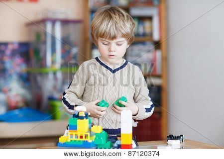 Kid Boy Playing With Lots Of Colorful Plastic Blocks Indoor