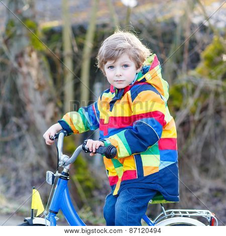 Kid Boy In Safety Helmet And Colorful Raincoat Riding Bike, Outdoors.