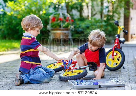 Father Teaching Two Little Kid Boys To Repair Chain On Bikes