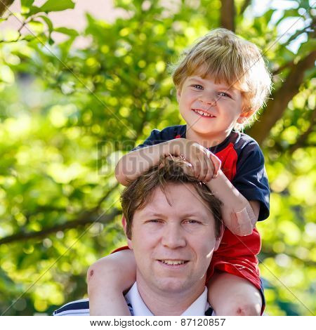 Father Carrying Child On His Shoulders In The Park