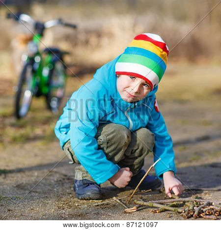 Cute Little Boy Playing With Wooden Sticks In City Park, Outdoors.