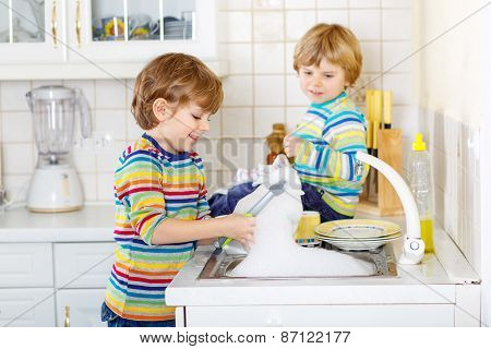 Two Little Blond Kid Boys Washing Dishes In Domestic Kitchen