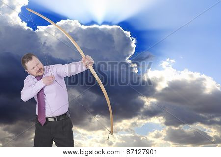 Businessman practicing archery and clouds in background