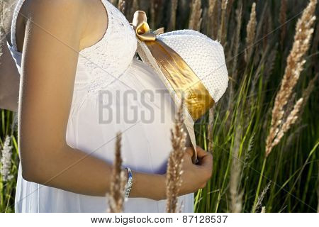 Pregnant  woman's belly with the hat in sunbeams