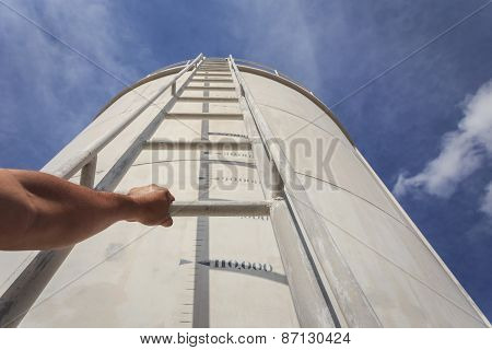 Hand Holding Ladder On Big Water Tank