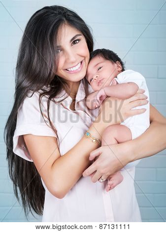 Portrait of beautiful cheerful mother with cute little baby on hands over blue wall background, enjoying parenthood, love and happiness concept