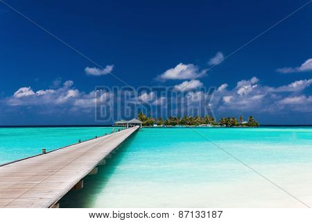 Wooden jetty to a tropical island over amazing lagoon in Maldives