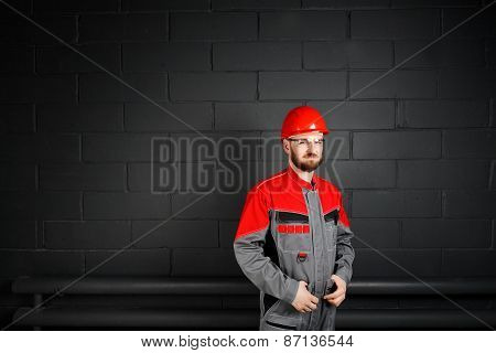 Portriat Of Smiling Man Wearing Overalls Near Brick Wall And Eyeglasses