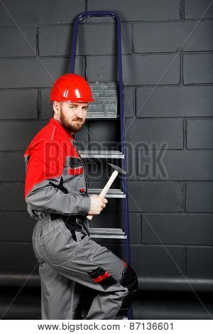 Man Wearing Overalls With Red Helmet And Hummer Near Brick Wall