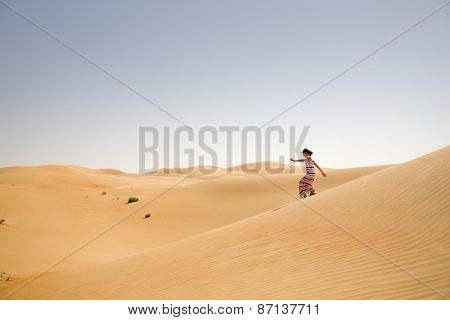 Young girl plays among sand dunes in desert
