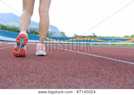 oung fitness woman runner legs running on track