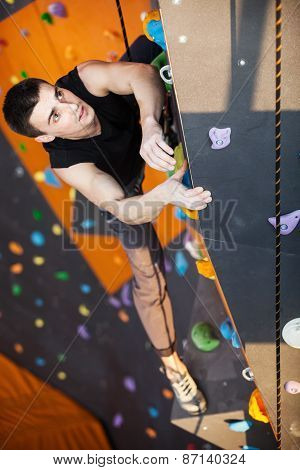 Young man practicing top rope climbing