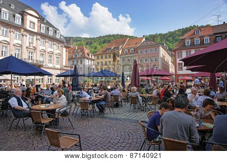 People In Outdoor Cafe On Central Square In Heidelberg