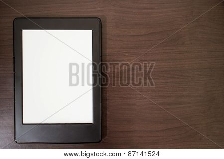 E-book reader on wooden table background with copy space