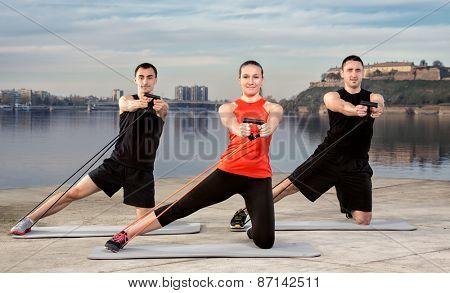 Three young people exercising, stretching band training