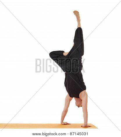 Flexible yoga man doing handstand in studio