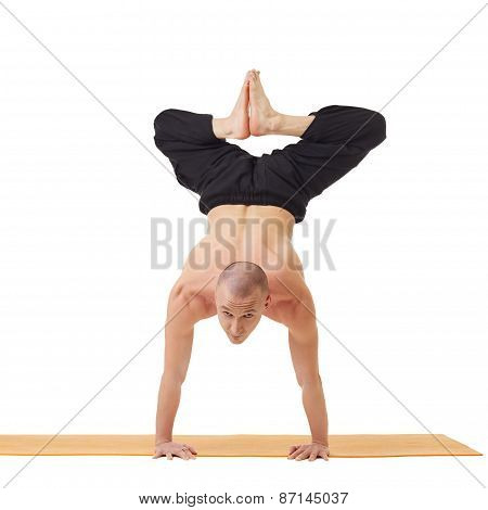 Yogi looking at camera while doing handstand