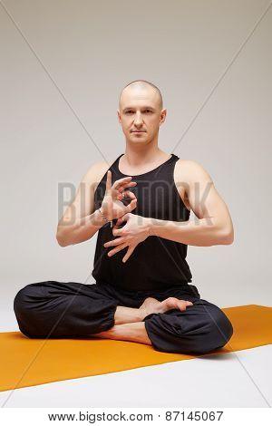 Handsome yogi posing at camera while meditating