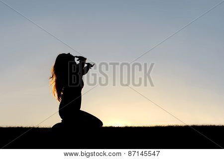 Silhouette Of Woman Kneeling In Prayer And Surrender