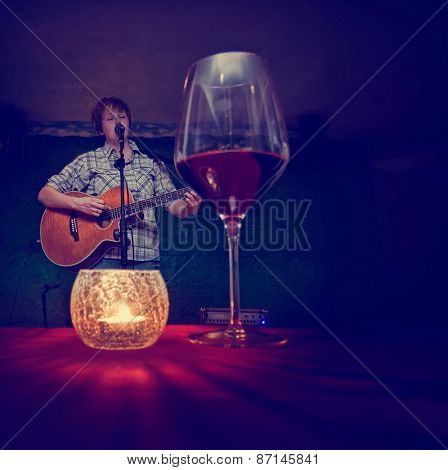 a girl in a bar playing the guitar and singing toned with a retro vintage instagram filter app or action