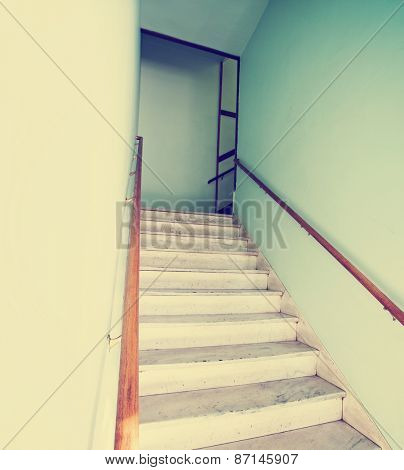 an empty stairwell with a wooden hand rail toned with a retro vintage instagram filter effect app or action