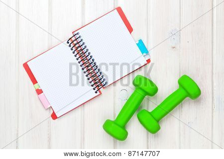 Dumbells and notepad for copy space. Fitness and health