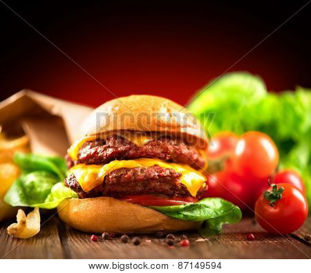 Hamburger with fries on wooden table. Cheeseburger on fresh buns with succulent beef patties and fresh salad ingredients served with French Fries on crumpled brown paper on a rustic wood table