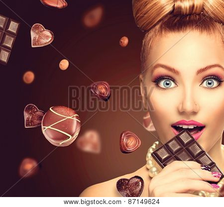 Beauty fashion model girl eating chocolate. Beautiful Surprised young woman takes chocolate sweets. Funny girl, professional make up and bow hairstyle. Diet,dieting concept